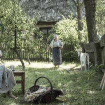 Stulecie Winnych, skansen w Sierpcu, fot. H.KOMERSKI, scena w sadzie, kobieta karmi dzicko piersią, mężczyzna naprawia płot