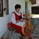Miodobranie w skansenie w Sierpcu 2012 - kobieta w stroju ludowym przy kołowrotku