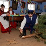"""Wystawa """"Boże Narodzenie na Mazowszu"""" 2012, skansen w Sierpcu - w chałupie, mężczyzna przygotowuje choinkę, kobiety wykonują ozdoby"""