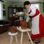 Majówka 2013, skansen w Sierpcu - kobieta w stroju ludowym wiruje śmietanę w centryfudze