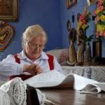 Majówka 2013, skansen w Sierpcu - kobieta w stroju ludowym wycina z papieru firany