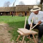 Majówka 2013, skansen w Sierpcu - mężczyzna w stroju ludowcym wynuje meble z drewna