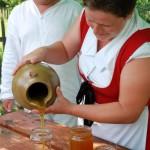 Miodobranie 2013, skansen w Sierpcu - kobieta w stroju ludowym nalewa do słoików miód