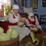 Wykopki 2013, skansen w Sierpcu - kobiety w strojach ludowych obierają kapustę, pokaz kiszenia kapusty