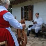 Wykopki 2013, skansen w Sierpcu - kobieta przędzie wełnę, mężczyzna czesze wełnę
