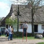 Gry i zabawy wielkanocne 2014, skansen w Sierpcu - zwiedzający uczą się chodzić na szczudłach