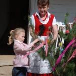 Gry i zabawy wielkanocne 2014, skansen w Sierpcu - dziewczynka dekoruje zieloną gałąź, tak zwanego gaika