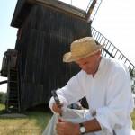 Żniwa 2014, skansen w Sierpcu - mężczyzna w stroju luodwym przy wiatraku, ostrzy dłutem kamienie młyńskie