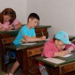 Dzień Dziecka 2014, skansen w Sierpcu - dzieci siedzą w ławkach w dawnej szkole, uczą się pisać stalówkami