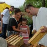 Miodobranie 2014, skansen w Sierpcu - pszczlarz w strju ludowym pokazuje zwiedzającym ramki z miodem