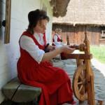 Majówka 2014, skansen w Sierpcu - kobieta w stroju ludowym przędzie wełnę na kołowrotku