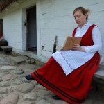 Majówka 2014, skansen w Sierpcu - kobieta w stroju ludowym czytaja bajki