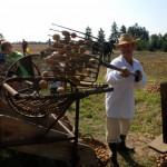 Wykopki 2014, skansen w Sierpcu - mężczyna w stroju ludowym wrzuca ziemniaki do sortownika