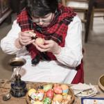 Niedziela Palmowa 2018, skansen w Sierpcu - kobieta w stroju ludowym maluje jaja woskiem