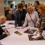 Koncert Marcina Wyrostka, sala widowiskowa Hotelu Skansen - przy stole siedzi Marcin Wyrostek, daje autografy