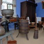 Zagroda z Jonnego, ekspozycja przetwórstwa mleka po lewej centryfuga do wirowania śmietany, pośrodku baran do masła (rodzaj masielnicy), obok kierzanka do masła, po prawej druga centryfuga
