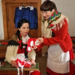 Majówka 2019, dzień drugi, skansen w Sierpcu - w wiejskiej izbie lekcyjnej, dwie kobiety w strojach ludowych, pokaz wykonywania kotylionów