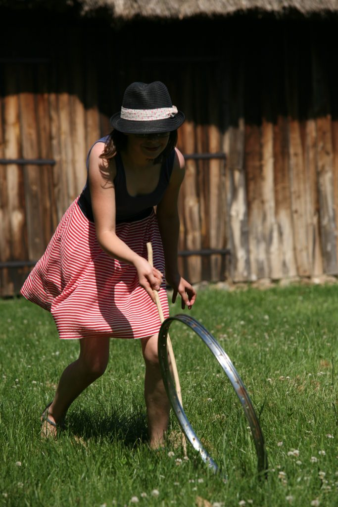 Dawna zabawa, dziewczynka toczy obręcz - Skansen w Sierpcu