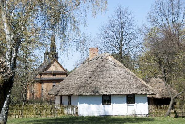 Widok na wiejska chałupę i kościół wiosną - Skansen w Sierpcu