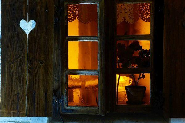 Okno w chałupie wiejskiej, wewnątrz świeci się lampa naftowa - Skansen w Sierpcu