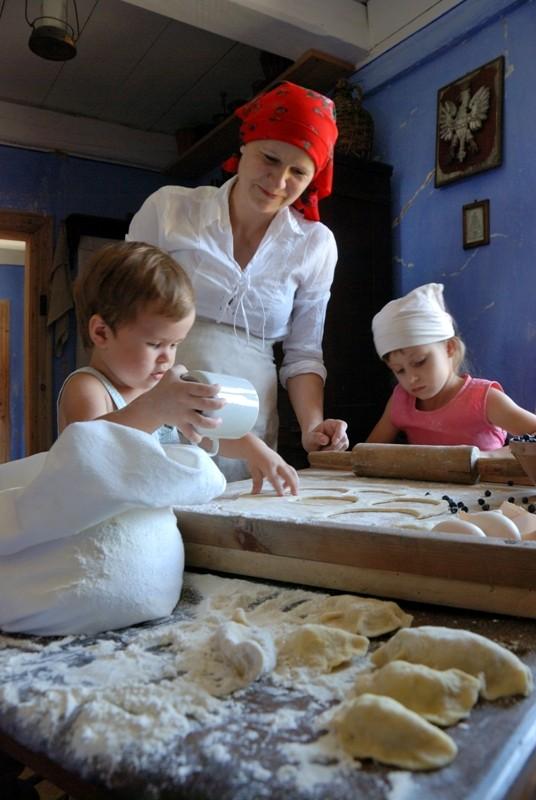 W chałupie wiejskiej, matka z dwojgiem dzieci lepi pierogi - Skansen w Sierpcu