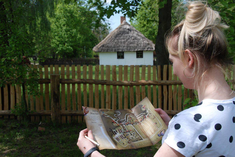 Kobieta z kartą gry terenowej, w tle wiejska chata - Skansen w Sierpcu