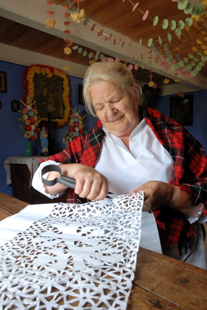 Kobiet w stroju ludowym wycina z papieru firany - Skansen w Sierpcu