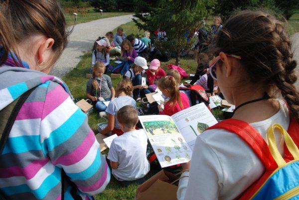 Dzieci z zeszytami ćwiczeń w parku dworskim - Skansen w Sierpcu