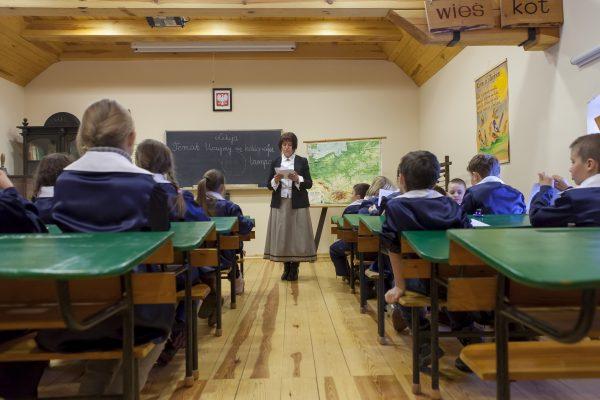 Dzieci w mundurkach na lekcji kaligrafii - Skansen w Sierpcu