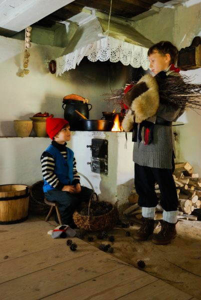 Dwóch chłopców w strojach ludowych z początku XX wieku w kuchni - Skansen w Sierpcu