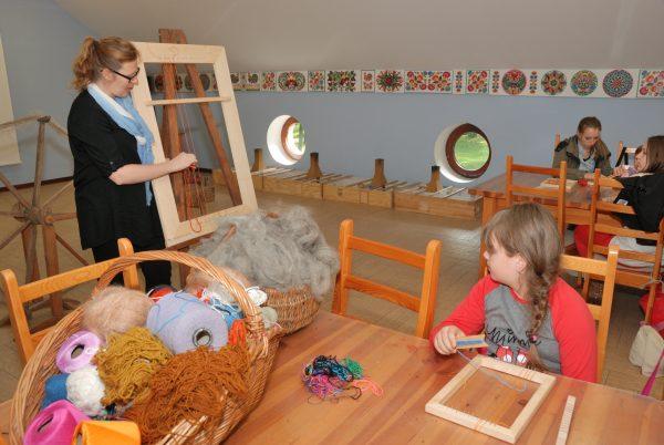 W sali edukacyjnej, prowadząca prezentuje metody tkania - Skansen w Sierpcu