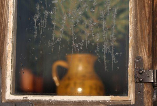 Zbliżenie, mróz na szybie, za oknem dzbanek - Skansen w Sierpcu