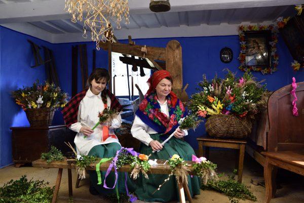 dwie kobiety przygotowują wielkanocne palmy w wiejskiej izbie