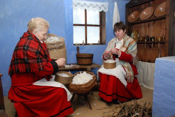dwie kobiety, które drą pierze w wiejskiej izbie