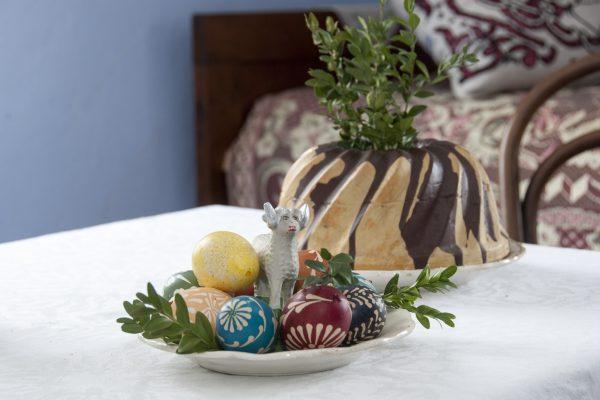 Na wielkanocnym stole na talerzu leżą malowane jajka, a za nimi baba wielkanocna