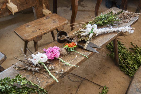 materiały i ozdoby potrzebne do wykonania wielkanocnej palmy leżące na ławie w wiejskiej izbie