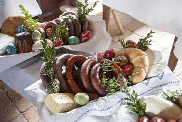widok z góry na wielkanocny stół: kiełbasy, pieczywo i jajka