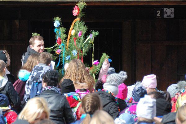 """grupa dzieci niosąca marzannę podczas imprezy plenerowej """"Powitanie wiosny w skansenie"""""""