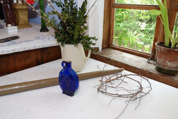 Na stole buteleczka z wodą święconą oraz korona cierniowa, przygotowane do rytuału święcenia ognia i wody.