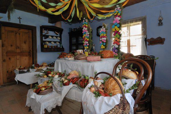 wnętrze chłopskiej izby, na stole oraz w koszykach przygotowane jedzenie do poświęcenia. m