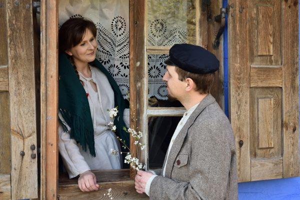 Dwoje zakochanych spogląda na siebie. Kobieta stoi w oknie, mężczyzna przy oknie.
