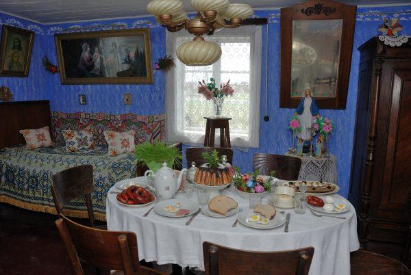 Wnętrze wiejskiej izby, na pierwszym planie nakryty stół z wielkanocnym śniadaniem
