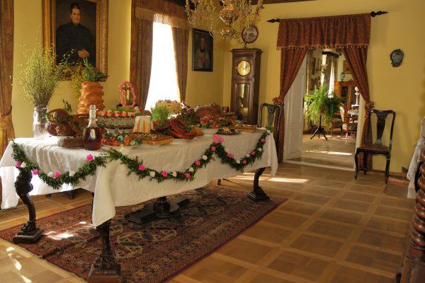 Wnętrze dworskiej jadalni, udekorany stół a na nim potrawy wielkanocne