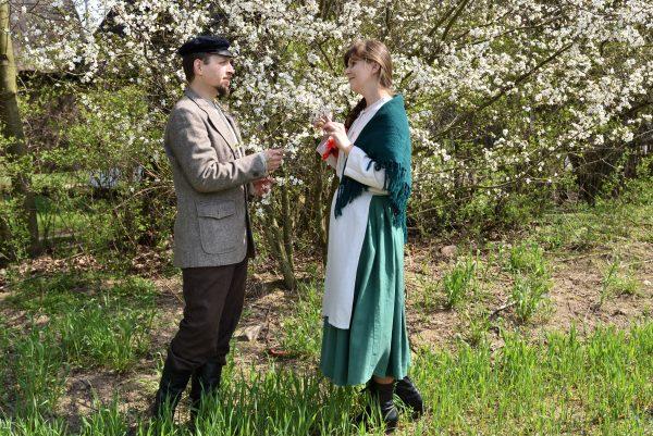 Mężczyzna i kobieta spoglądają na siebie stojąc przy kwitnącym drzewie.