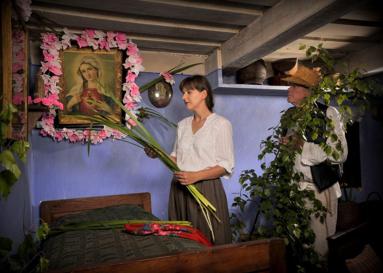 Młoda kobieta i starszy mężczyzna dekorują izbę zielonymi gałązkami