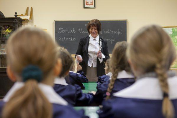 Kobieta prowadzi lekcję, dzieci siedzące w ławkach i ubrane w mundurki słuchają