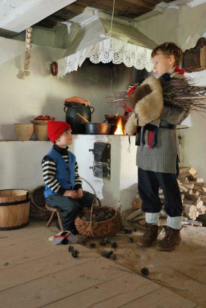 dwoje chłopców w wiejskiej izbie trzyma chrust na opał