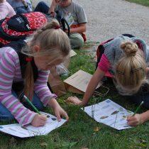 Dzieci siedzą na trawie, rozwiązują zagadki z zeszytu ćwiczeń - Skansen w Sierpcu