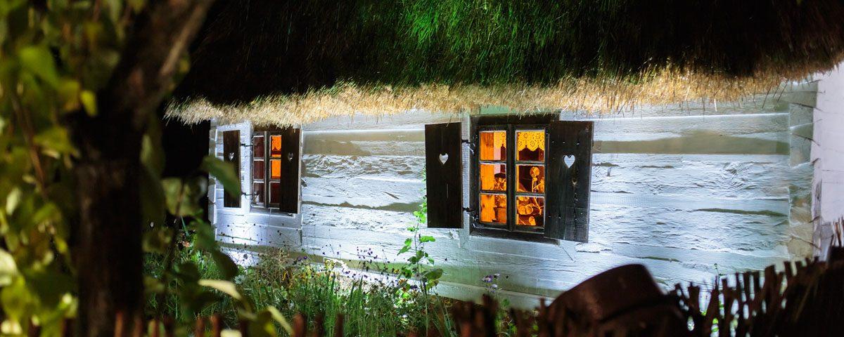 Wiejska chata nocą, kwiaty w ogrodzie, skansen w Sierpcu