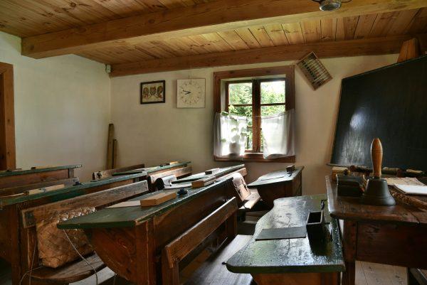 Izba lekcyjna z ławkami, tablicą i przyborami szkolnymi